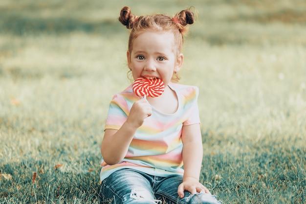 Een mooi klein meisje zit in het park op het gras met een rode lolly in haar handen. hoge kwaliteit foto