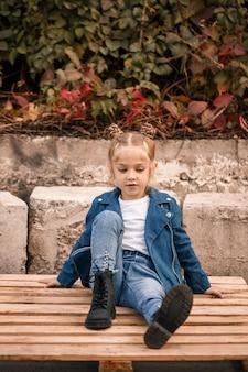 Een mooi klein meisje zit in stijlvolle kleding op houten pallets. stijlvol kind in een blauwe jas. casual stijl, mode voor kinderen, modieus pak, gelukkige jeugd