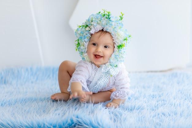 Een mooi klein meisje zit op een blauw pluizig tapijt met een hoed gemaakt van bloemen en lacht