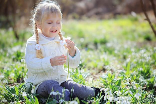 Een mooi klein meisje zit op een bloemenweide. een klein meisje in een witte gebreide trui overweegt een sneeuwklokje. pasen. lente zonnig bos