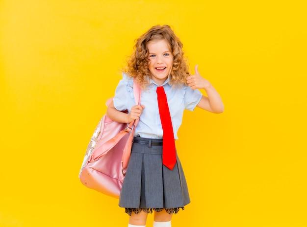 Een mooi klein schoolmeisje in een schooluniform, met een vrolijke glimlach. leuk schoolmeisje dat met blond haar roze aktentas op geïsoleerde gele achtergrond houdt Premium Foto