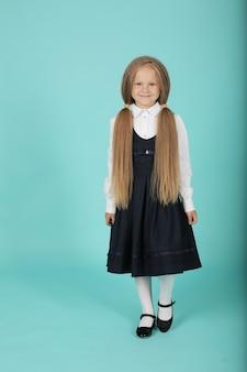 Een mooi lachend blond meisje in een wit overhemd en een grijze zomerjurk is een schoolmeisje