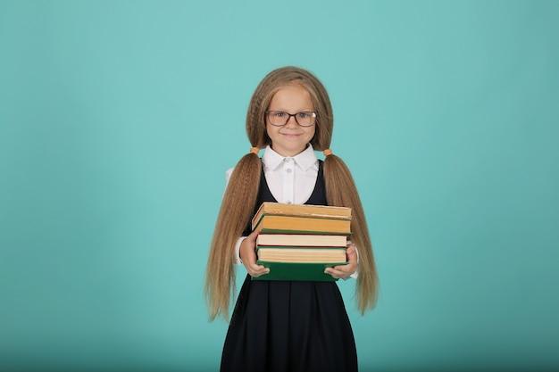 Een mooi lachend blond meisje met staartjes in een wit overhemd en een grijze zomerjurk een schoolg