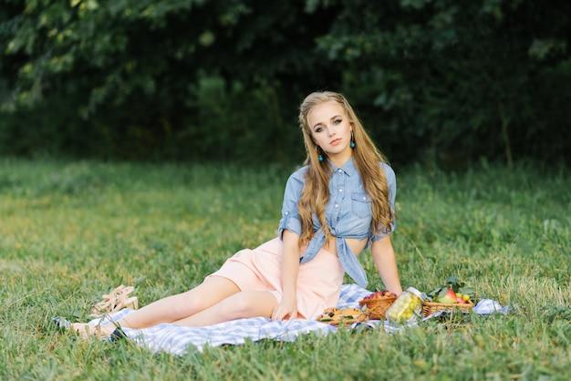 Een mooi lief meisje in een blauw denim shirt en een chiffon roze rok zit op een plaid op een zomerpicknick