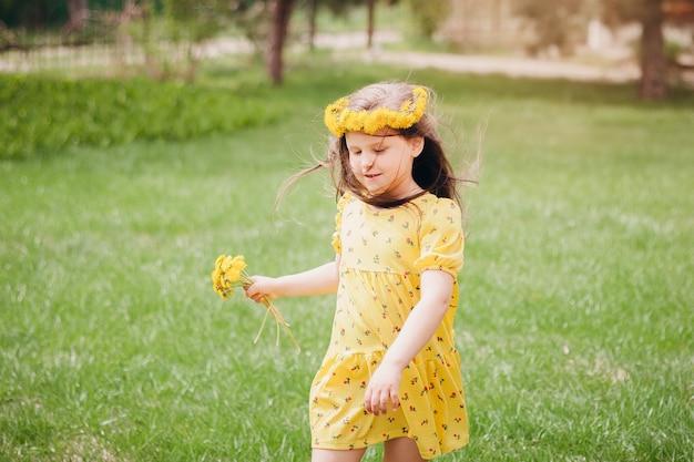Een mooi lief meisje in een gele jurk en met gele paardebloemen met haar dat in de wind vliegt een p...