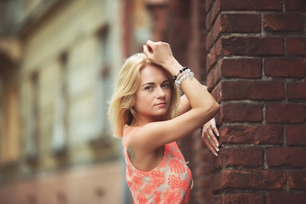 Een mooi meisje alleen in de buurt van grunge muur