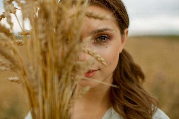 Een mooi meisje bedekte de helft van haar gezicht met een boeket oren.
