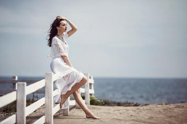 Een mooi meisje, bruid, in een witte jurk, blootsvoets, zittend op een witte schelp