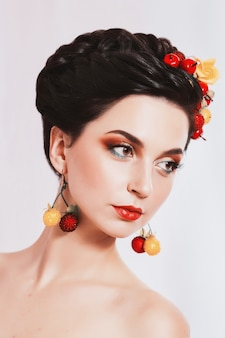 Een mooi meisje, brunette vrouw met bruine ogen met lichte make-up, make-up met bessen en bloemen in het haar, rode lippen, ongewone uitstraling