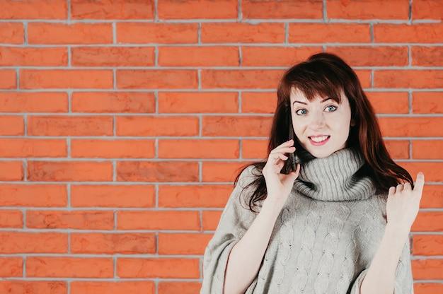 Een mooi meisje dat door mobiel spreekt, verrassend glimlachend, in een grijze trui