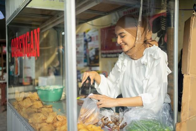 Een mooi meisje dat een hijab draagt terwijl ze een tang gebruikt, kiest gefrituurd voedsel dat de koper bestelt