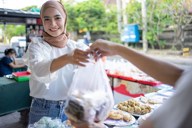 Een mooi meisje dat een hoofddoek draagt en een kraampje aan de kant van de weg verkoopt, geeft takjil eten