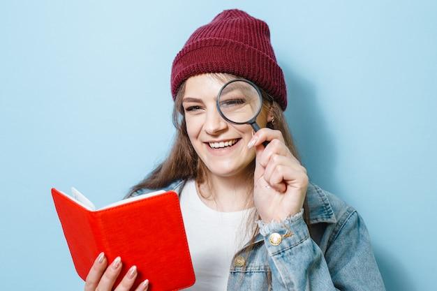 Een mooi meisje dat glimlacht en gebaren toont met een vergrootglas en een boek in haar hand tegen een blauwe achtergrond