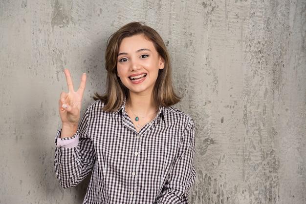 Een mooi meisje dat het teken van de twee vingersoverwinning toont.