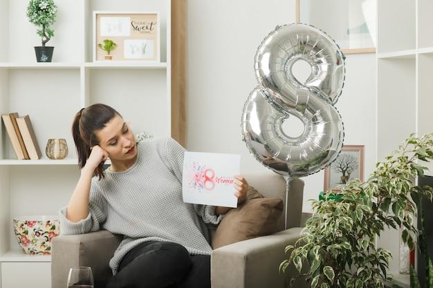 Een mooi meisje denken op een gelukkige vrouwendag die een wenskaart vasthoudt en bekijkt terwijl ze op een fauteuil in de woonkamer zit