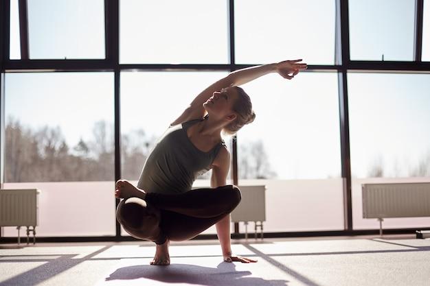 Een mooi meisje doet yoga tegen de achtergrond van panoramische ramen in de studio. het meisje voert balanceren op één been uit