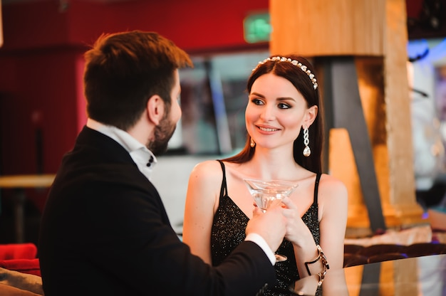Een mooi meisje drinkt martini in de lobby van het hotel