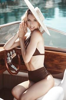 Een mooi meisje, een model in een badpak en een hoed met een brede rand