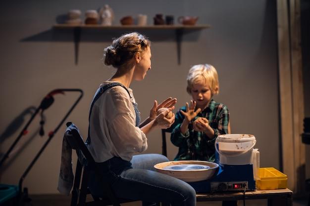 Een mooi meisje en een blonde jongen beeldhouwen een bord op een pottenbakkersschijf in een kunststudio.