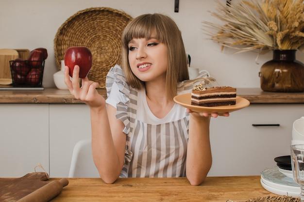 Een mooi meisje houdt een cake in de ene hand en een appel in de andere en denkt wat ze moet eten