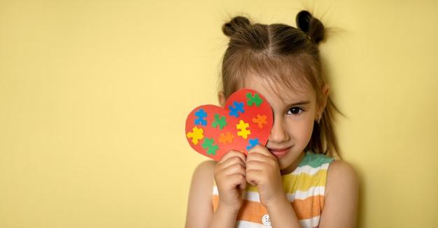 Een mooi meisje houdt een hart vast met kleurrijke puzzels in haar handen die één oog bedekken