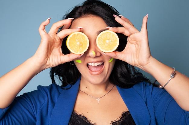 Een mooi meisje houdt twee sappige citroenen bij haar gezicht. citroen, gehalveerd.