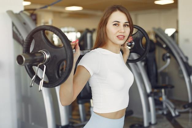 Een mooi meisje houdt zich bezig met een sportschool met een halter