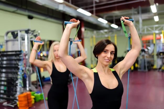 Een mooi meisje houdt zich bezig met een sportschool.