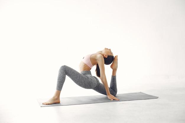 Een mooi meisje houdt zich bezig met een yogastudio
