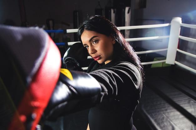 Een mooi meisje in bokshandschoenen slaat haar poten in de ring