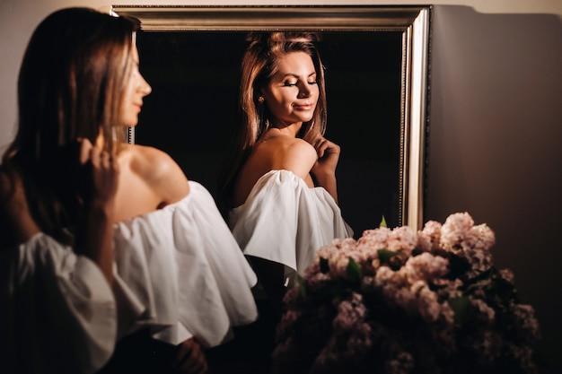 Een mooi meisje in de spiegel wordt thuis weerspiegeld. meisje voor de vakantie in de buurt van de spiegel thuis. een meisje in een witte jurk met lang haar poseert in de buurt van een grote spiegel thuis