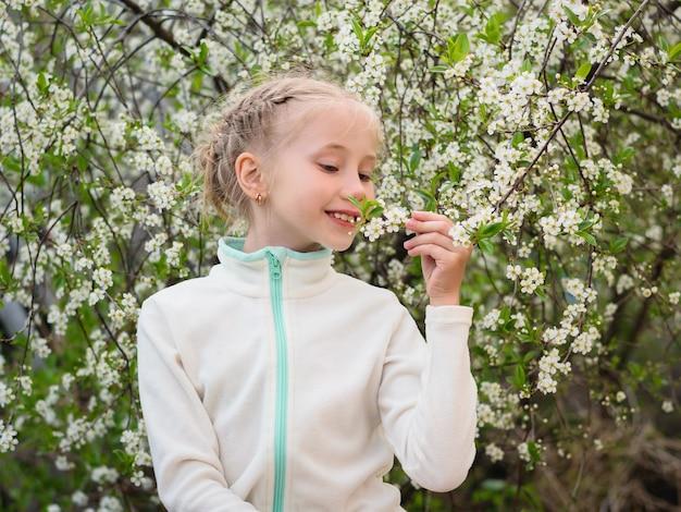 Een mooi meisje in een colbert geniet van de geur van kersen in de lentetuin.