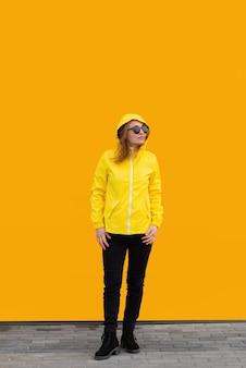 Een mooi meisje in een geel jasje en zonnebril met haar kap op oranje achtergrond