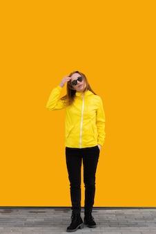 Een mooi meisje in een geel jasje en zonnebril stangind omhoog op oranje achtergrond