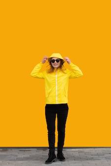 Een mooi meisje in een gele jas en zonnebril zet haar capuchon op een oranje achtergrond
