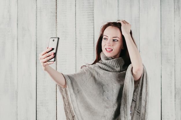 Een mooi meisje in een grijze trui, glimlachend en selfie makend