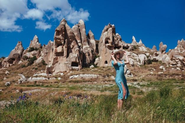 Een mooi meisje in een hoed en een turquoise jurk staat in een weiland tegen de achtergrond van het reliëf van capadocia
