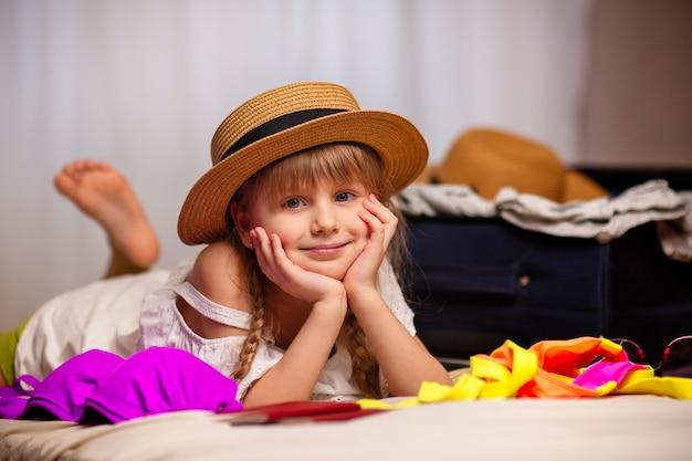 Een mooi meisje in een hoed klaar voor vakantie ligt glimlach op het bed een strandreis naar de zee bereidt bagage opheffing van beperkingen voor toeristen voor