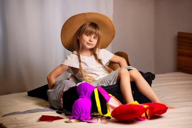 Een mooi meisje in een hoed klaar voor vakantie zit in een koffer op het bed een strandreis naar de zee bereidt bagage voor het openen van de grenzen van landen voor toeristen