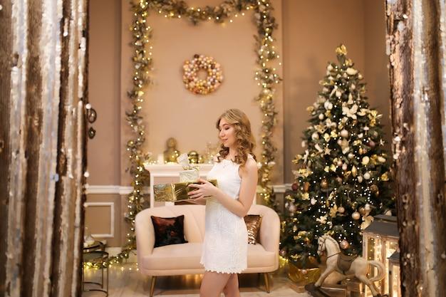 Een mooi meisje in een jurk staat met cadeautjes bij de boom in een luxe kerstinterieur