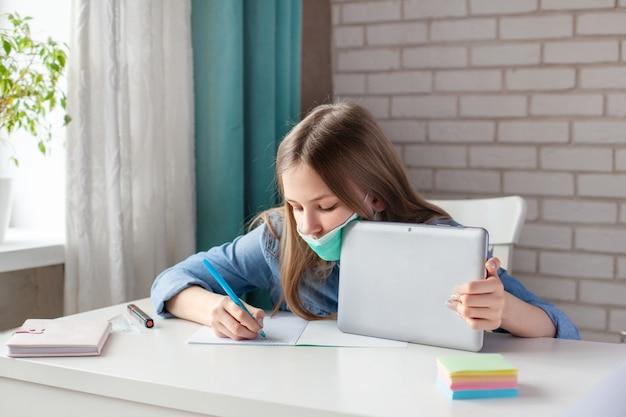 Een mooi meisje in een medisch masker studeert thuis met een digitale tablet-laptop en maakt huiswerk, schrijft het antwoord in een notitieblok. afstandsonderwijs, online onderwijs