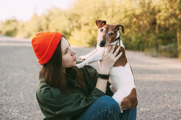 Een mooi meisje in een oranje hoed houdt haar hond in haar armen.