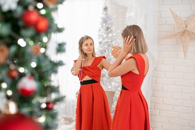 Een mooi meisje in een rode avondjurk bewondert zichzelf terwijl ze in de spiegel kijkt. een jonge glimlachende vrouw bereidt zich voor op de vakantie. de blonde in de rode jurk.