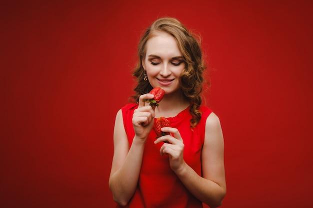 Een mooi meisje in een rode jurk op een rode achtergrond heeft een aardbei in haar handen en glimlacht