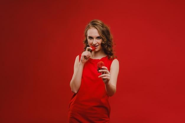 Een mooi meisje in een rode jurk op een rode achtergrond heeft een aardbei in haar handen en glimlacht.