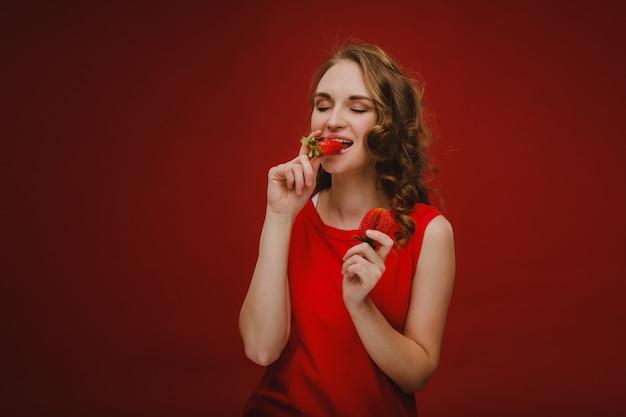 Een mooi meisje in een rode jurk op een rode muur heeft een aardbei in haar handen en glimlacht