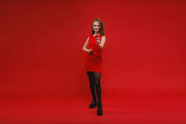 Een mooi meisje in een rode jurk op een rood heeft een aardbei in haar handen en glimlacht.