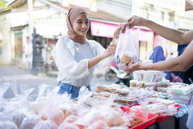 Een mooi meisje in een sluier koopt takjil-eten van een kraamverkoper langs de weg