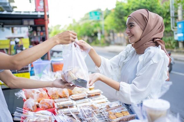 Een mooi meisje in een sluier koopt takjil-eten