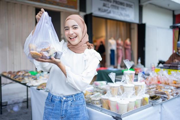 Een mooi meisje in een sluier koopt verschillende soorten takjil-eten